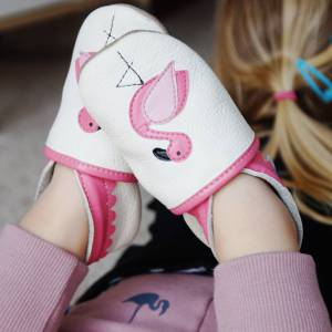 na nóżkach dziewczynki widać miekkie i lekkie skórzane kapcie dla dzieci do przedszkola białe flamingi paputki